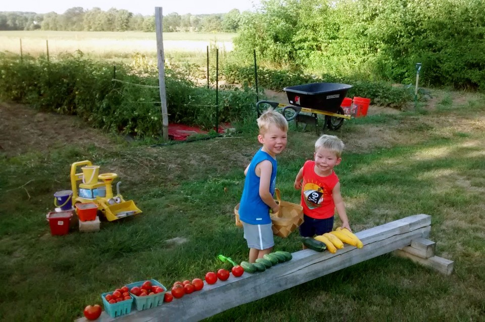 Jacob and Nolan lining up vegetables on a wood bench