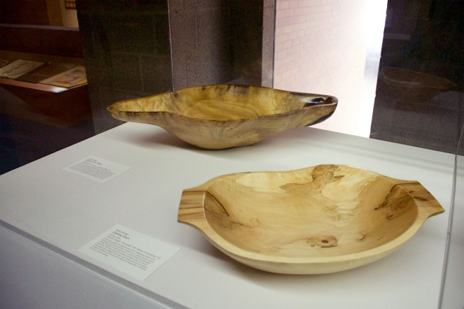 Two wooden bowls in a glass display case